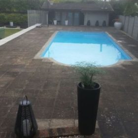 Before pressure washing on a patio surrounding a swimming pool in Surrey.