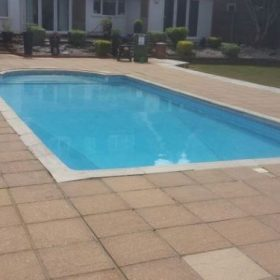 After pressure washing on a patio surrounding a swimming pool in Surrey.