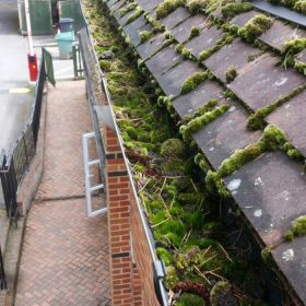 Gutter on a commercial property in Surrey before cleaning